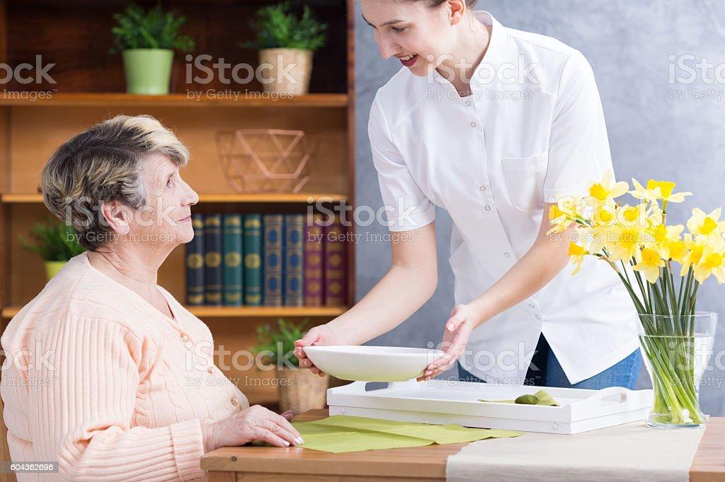 Home nurse serving soup stock photo