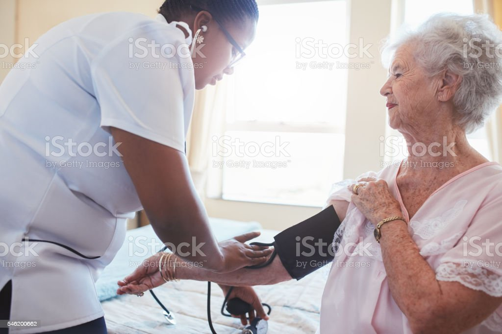 Home nurse taking patient's blood pressure stock photo