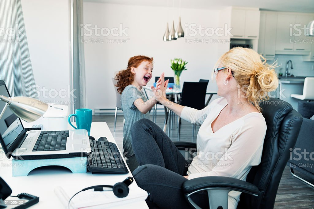 Home office, single mother conciliating work and family. stock photo
