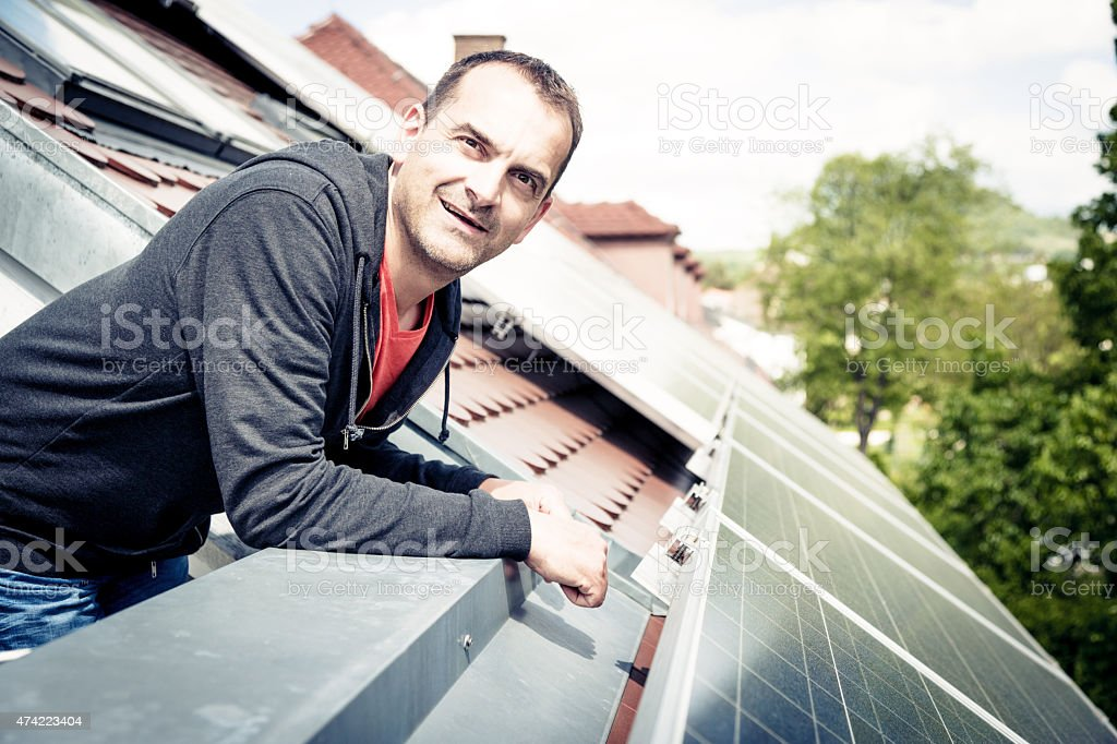 home owner is happy with solar panels on his roof stock photo