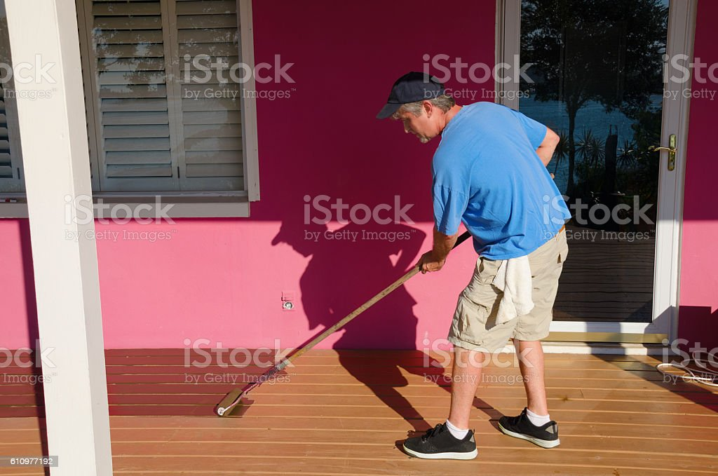 DIY home owner painting staining wooden deck stock photo