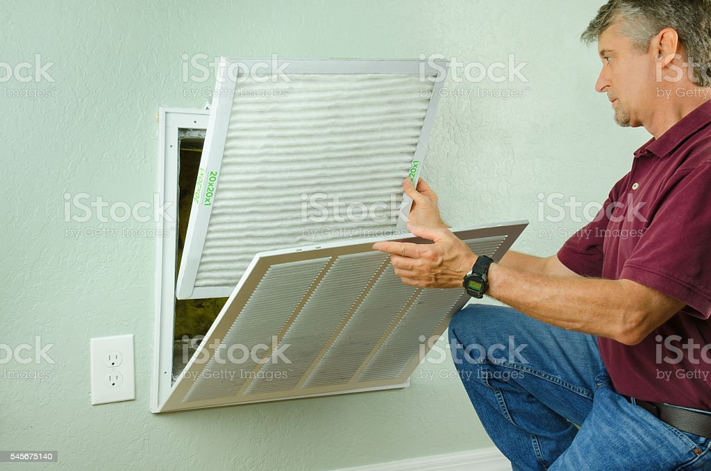 Home owner putting new air filter on air conditioner stock photo