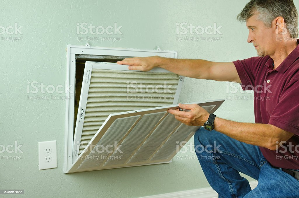Home owner replacing air filter on air conditioner stock photo