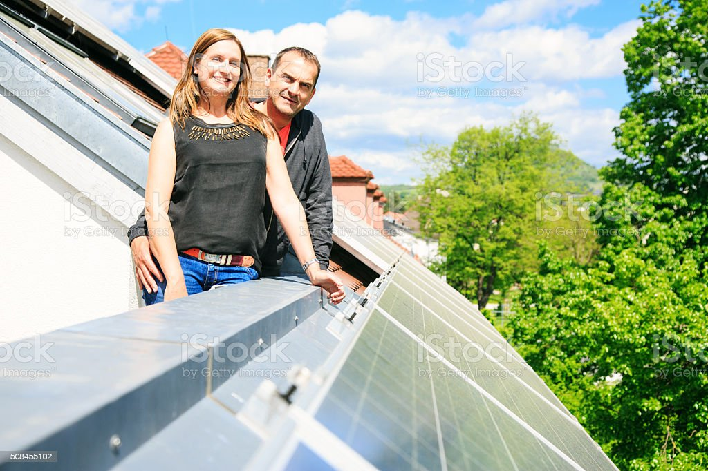 home owners are happy with solar panels on his roof stock photo
