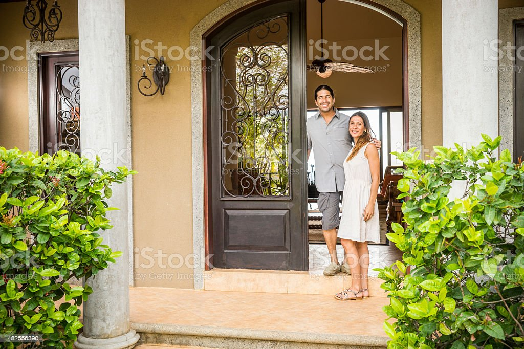 Home owners outside their home in Latin America stock photo