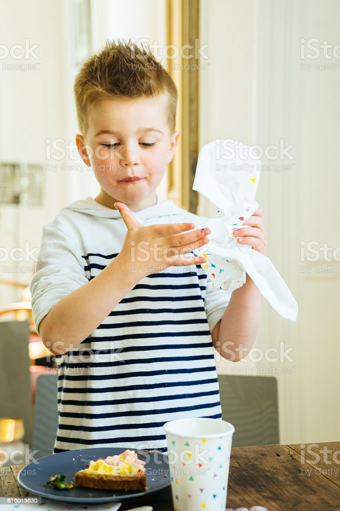 Home party with family, little boy eating cake stock photo