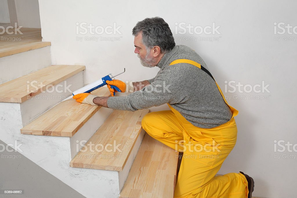 Home renovation, caulking wooden stairs with silicone stock photo