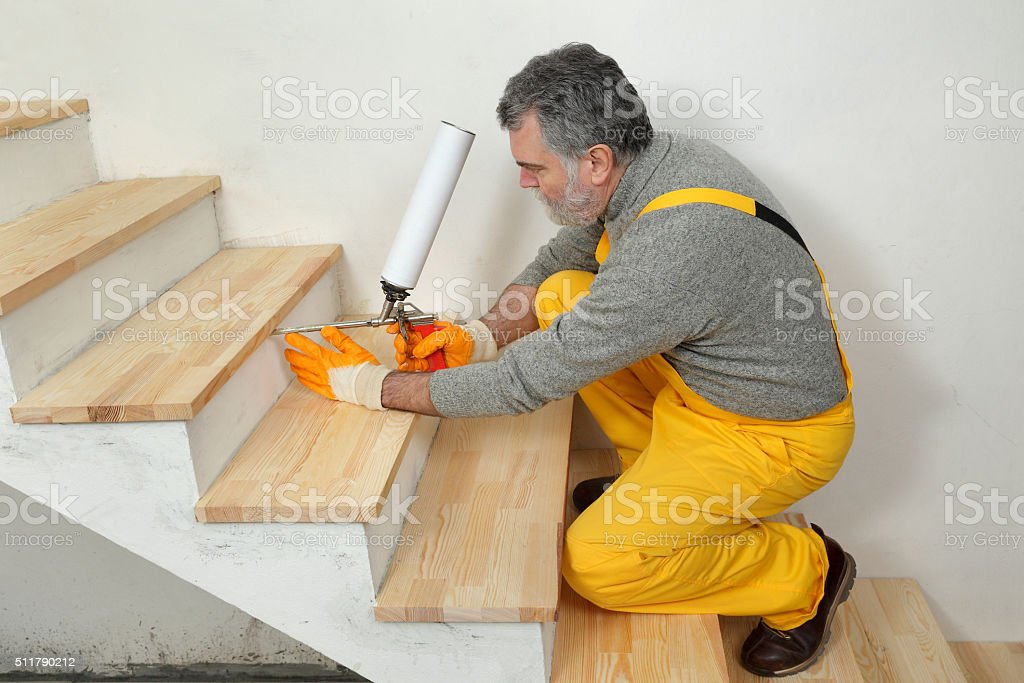 Home renovation, wooden stairs fix with polyurethane spray gun stock photo