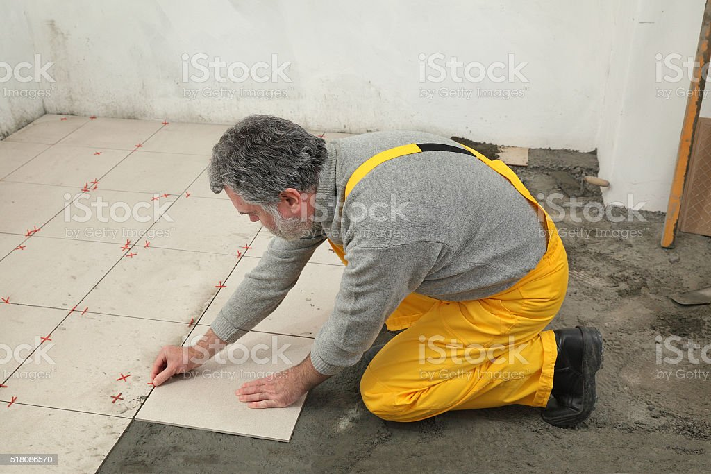Home renovation, worker placing tile stock photo