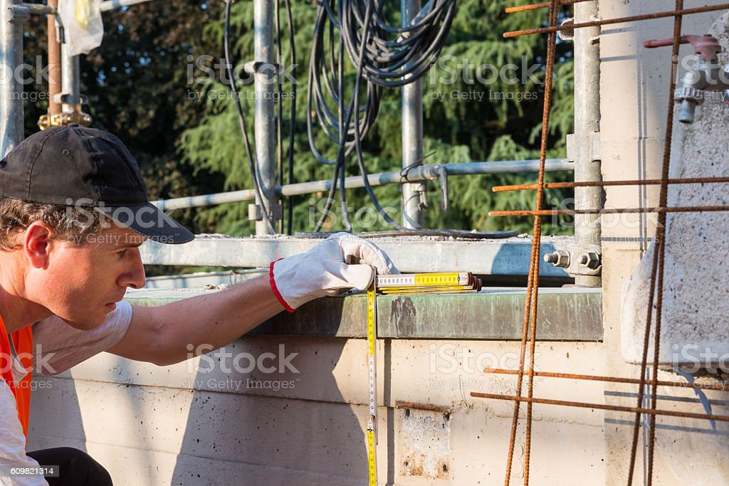 Home repair, bricklayer with a folding meter stock photo