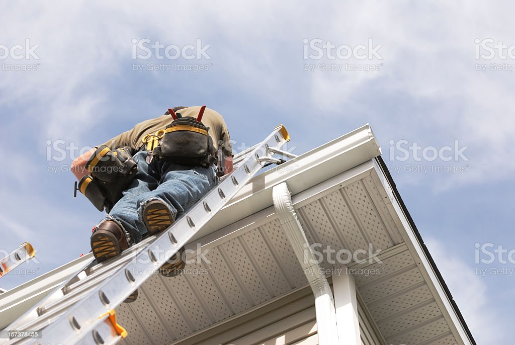 Home Repairs Handyman Up a Ladder outdoors stock photo