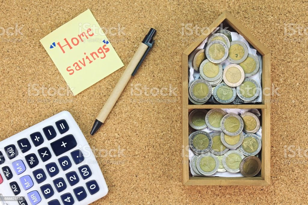 Home saving concept, Money saving for dream home. Model house and coins on wood board. Calculate for home budget. stock photo