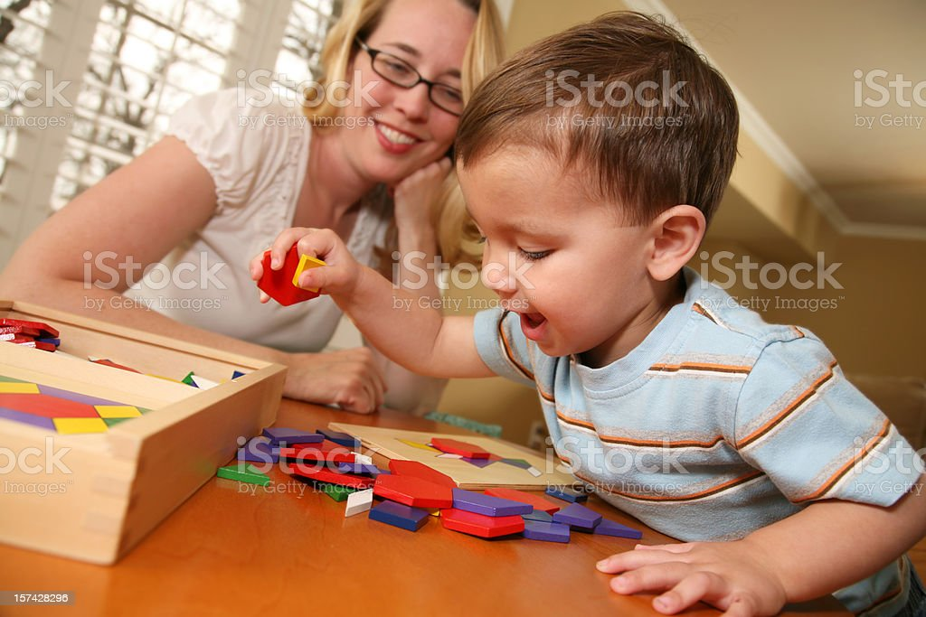 Home School Mom Helping Toddler Put Puzzle Together stock photo