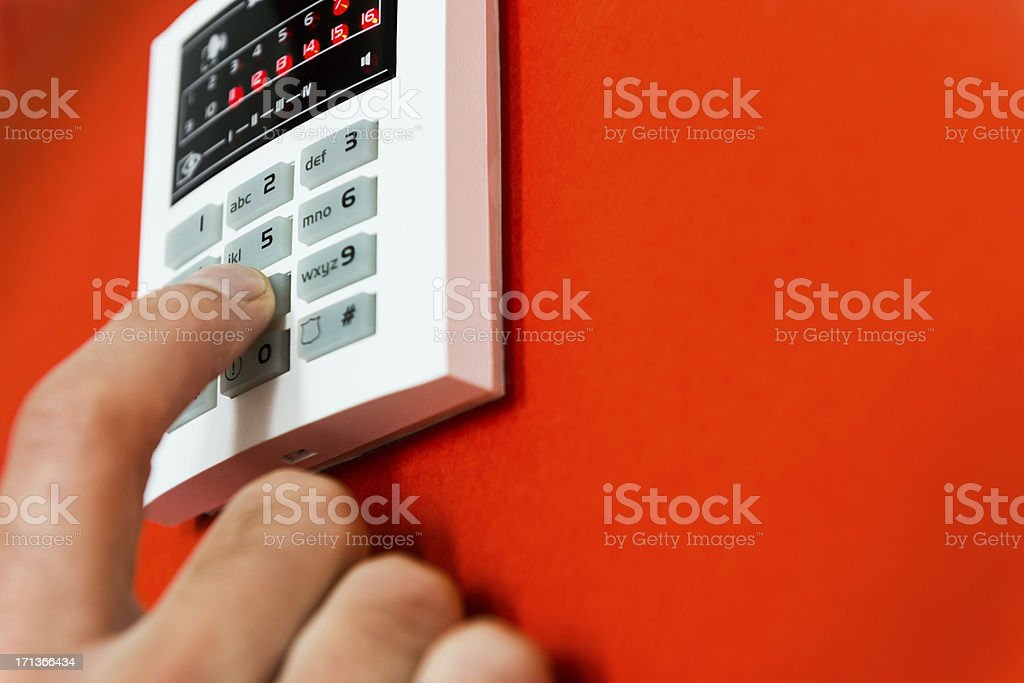 Home security system, man's hand activating burglar alarm royalty-free stock photo