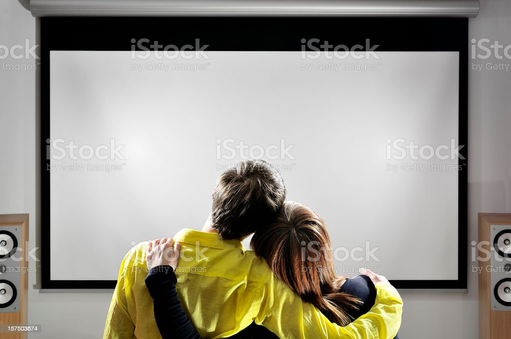 Home theater, hugging couple is watching movies on huge screen stock photo