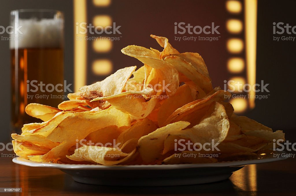 Home Theater Snack of Beer and Potato Chips Crisps royalty-free stock photo
