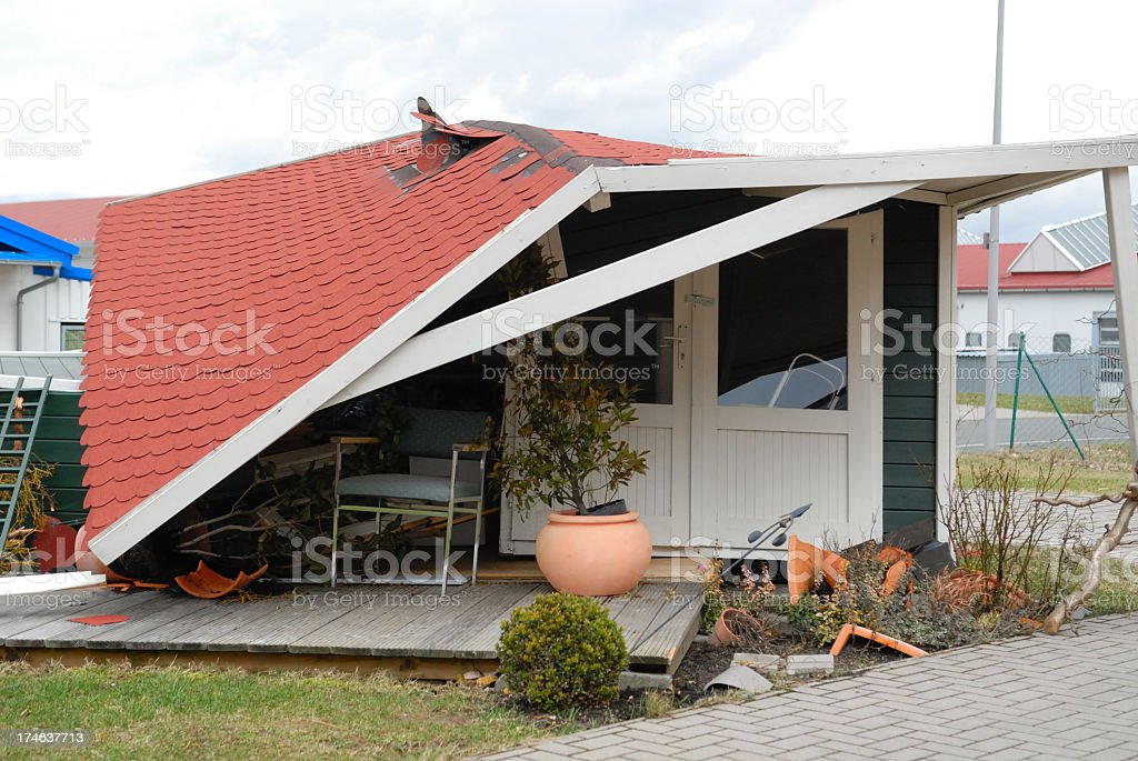 Home with fallen roof and broken pots after a storm stock photo