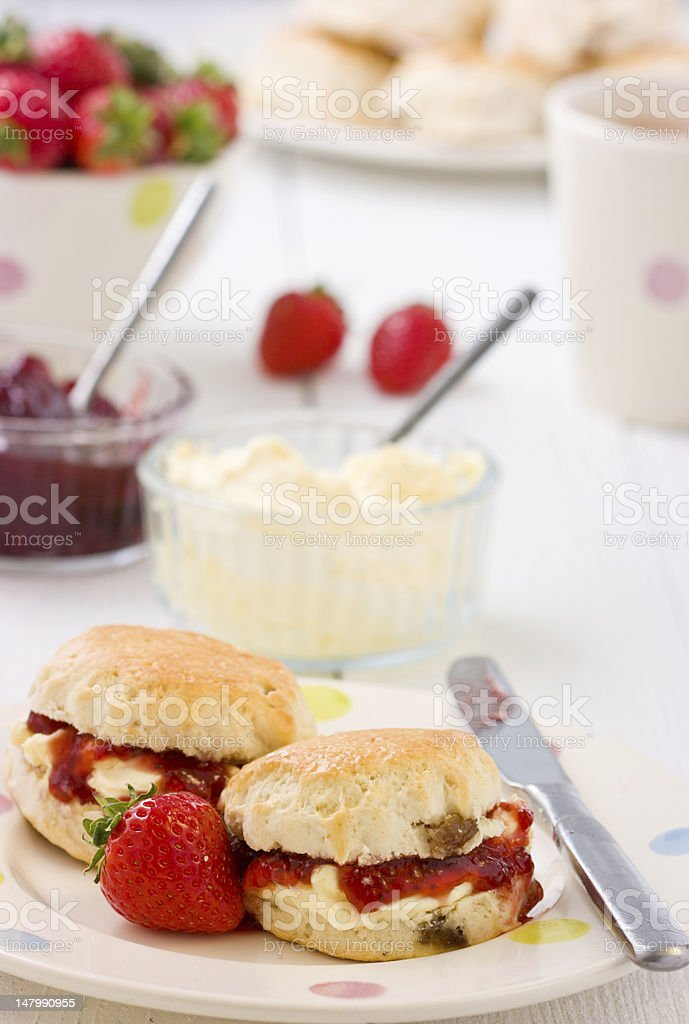 Home-baked scones strawberry jam, clotted cream strawberries, and tea. stock photo