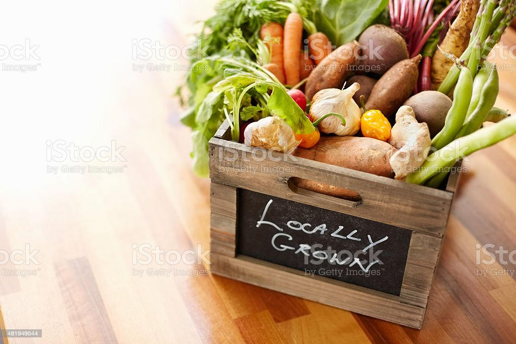 Homegrown vegetables in wooden crate at kitchen stock photo