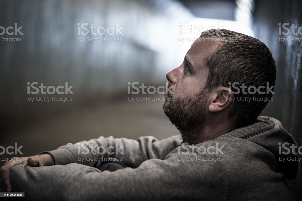 Homeless adult male sitting in subway tunnel begging for money stock photo