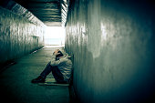Homeless adult male sitting in subway tunnel, hands on head