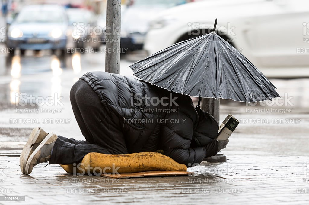 Homeless beggar with umbrella in the rain stock photo