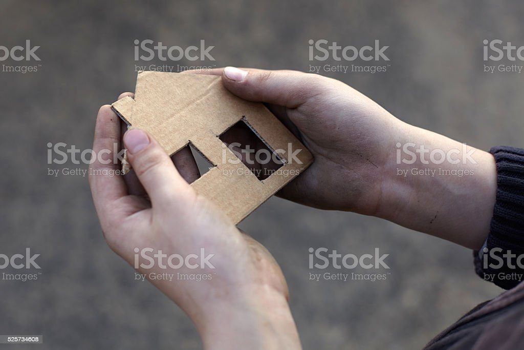 homeless boy holding a cardboard house stock photo