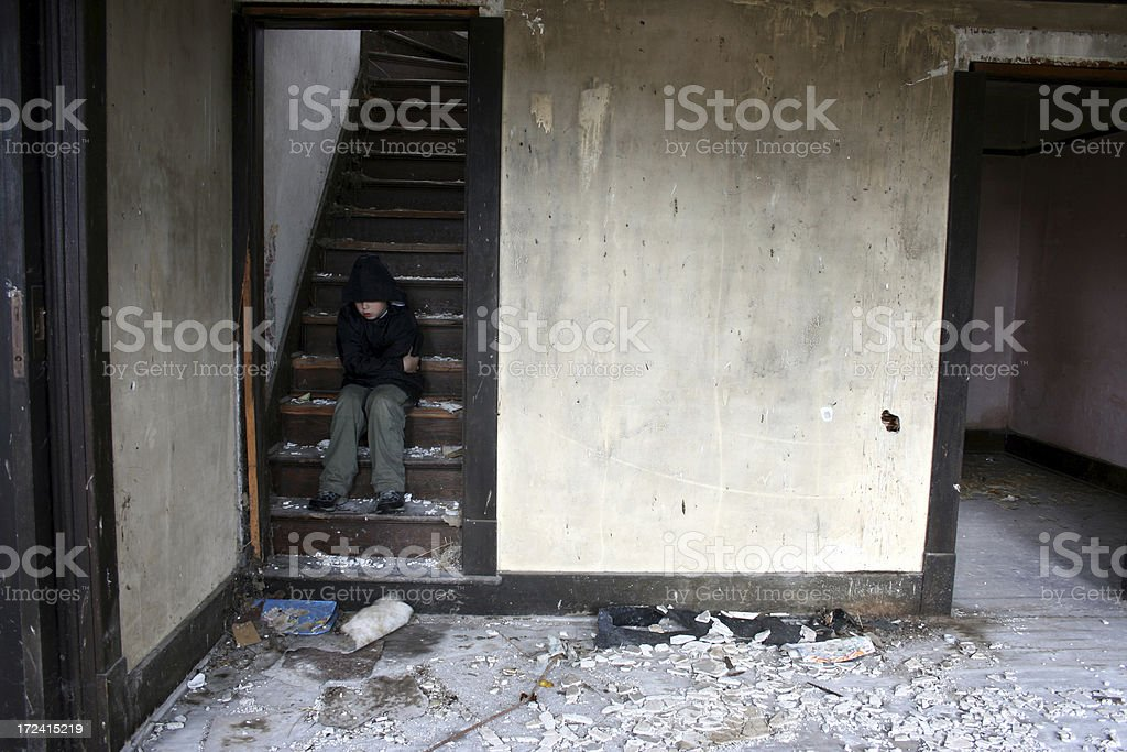 Homeless boy sitting on stairs of abandoned water damaged home royalty-free stock photo