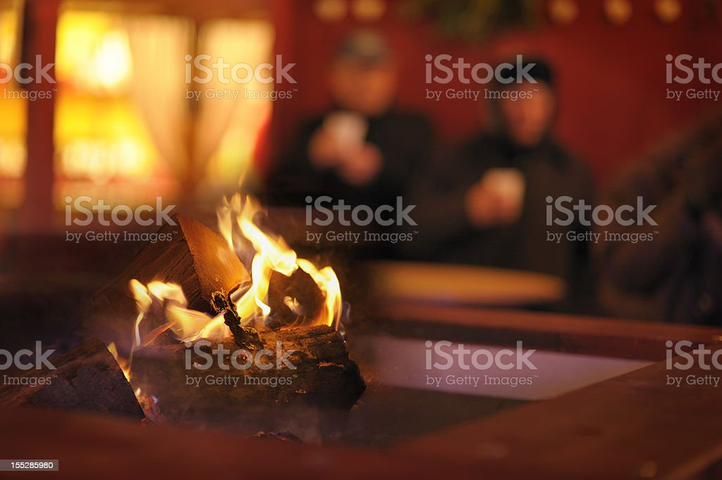 Homeless couple by log fire outdoors stock photo