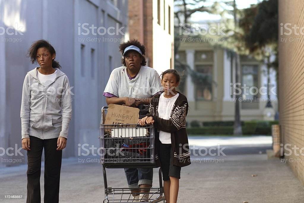 Homeless Family Pushes Cart in Alley royalty-free stock photo