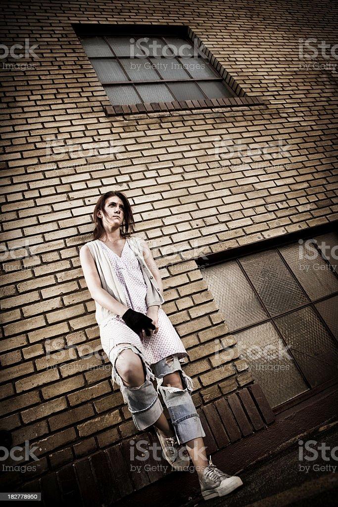 Homeless Girl against Brick Building royalty-free stock photo