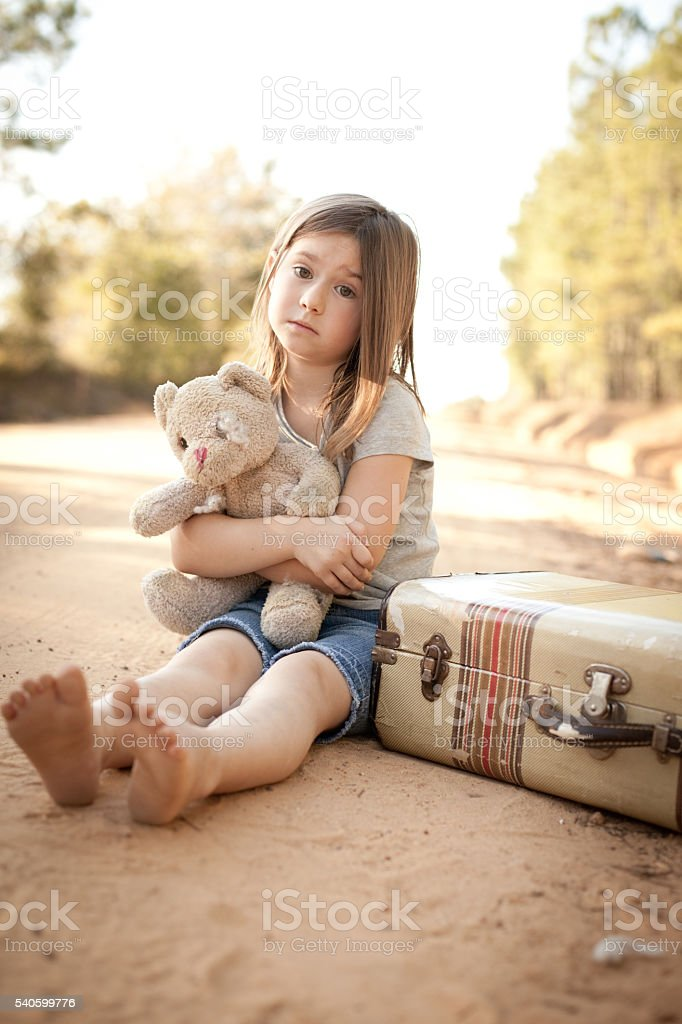 Homeless Girl Hugging Teddy Bear by Suitcase on Dirt Road stock photo