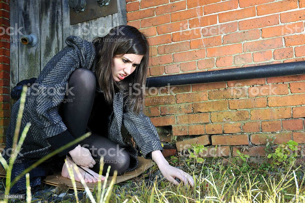 Homeless Girl Scrounging on the Ground stock photo