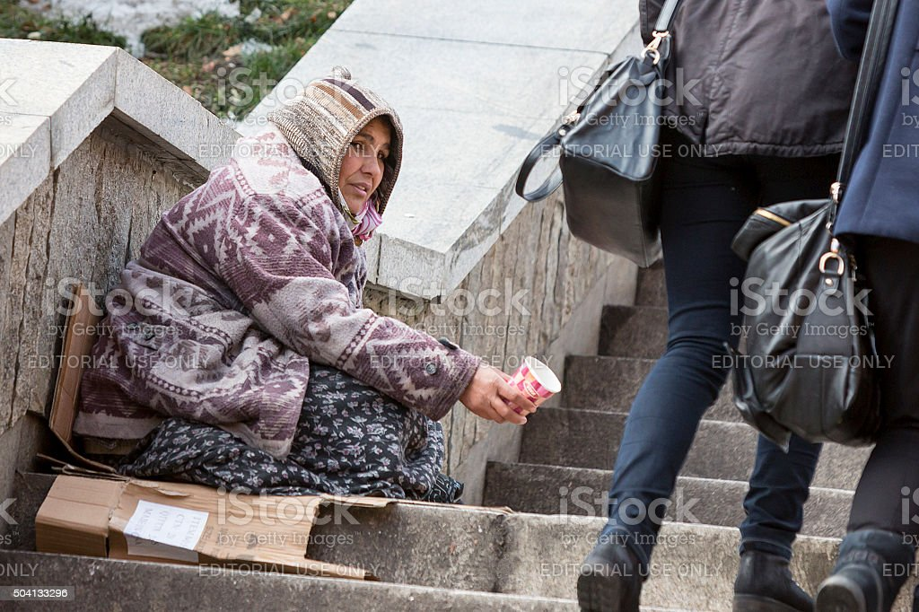 Homeless gypsy woman begging for money stock photo