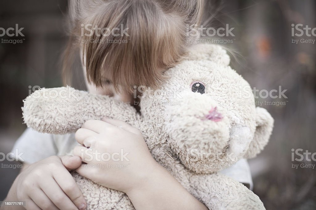 Homeless Little Girl Hugging Old, Raggedy Teddy Bear stock photo