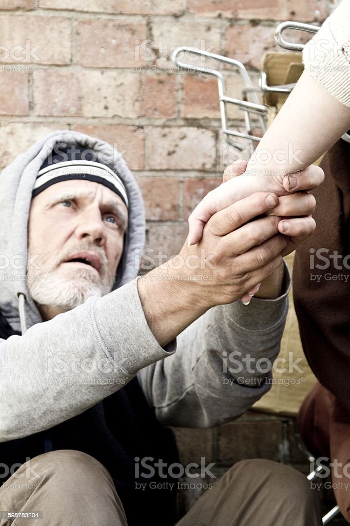 Homeless man and passer by stock photo