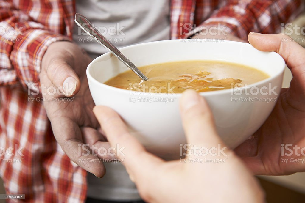 Homeless Man Being Handed Bowl Of Soup By Volunteer stock photo