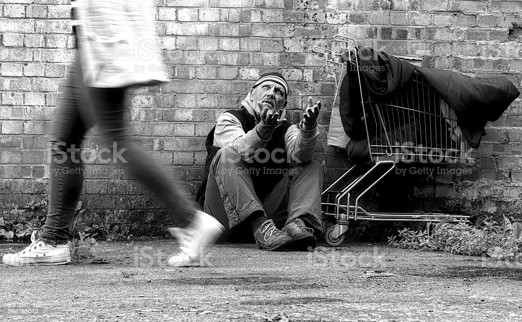 homeless man being ignored stock photo