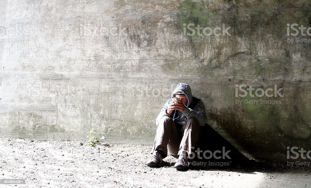 homeless man crouched against wall stock photo