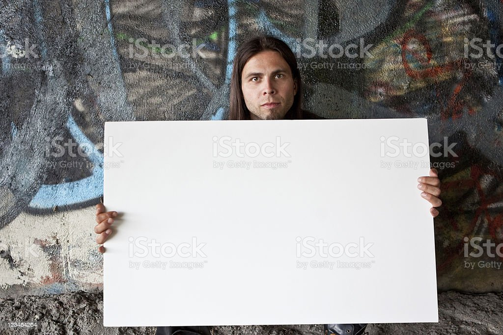 Homeless man holding a blank sign stock photo
