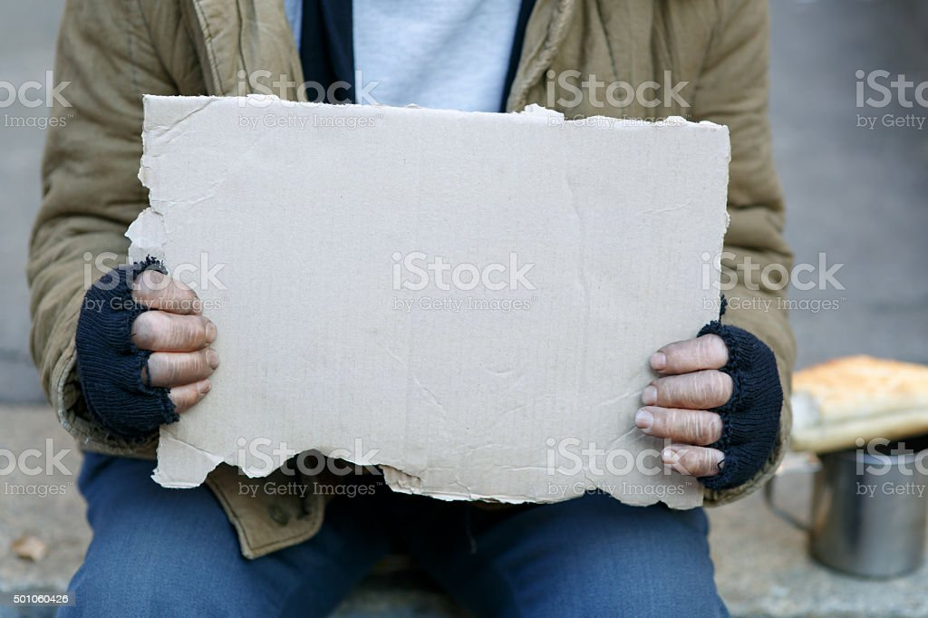 Homeless man holding a cardboard sign stock photo