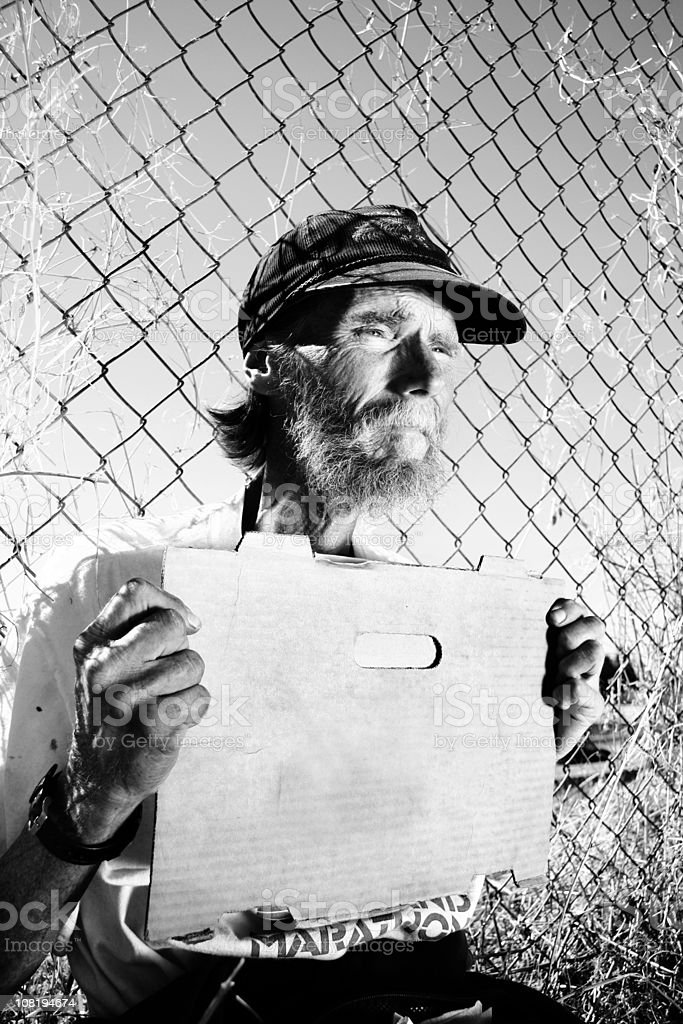 Homeless Man Holding Blank Sign Sitting Against Fence royalty-free stock photo