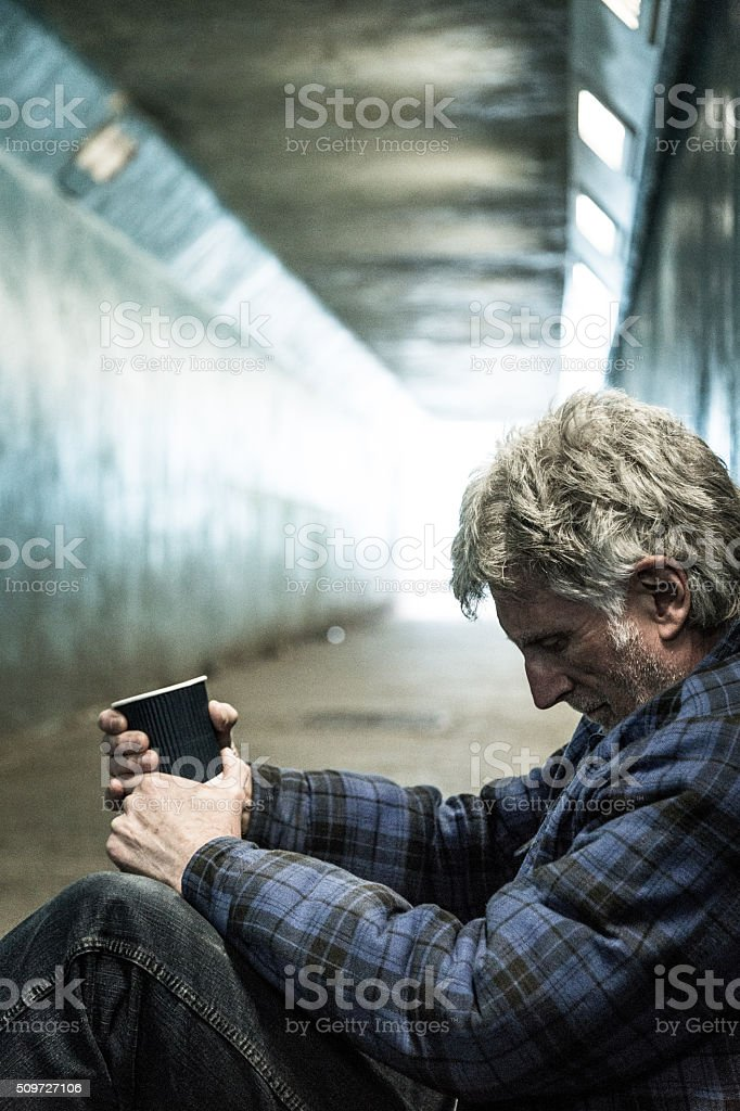 Homeless man in subway tunnel begging with paper cup stock photo