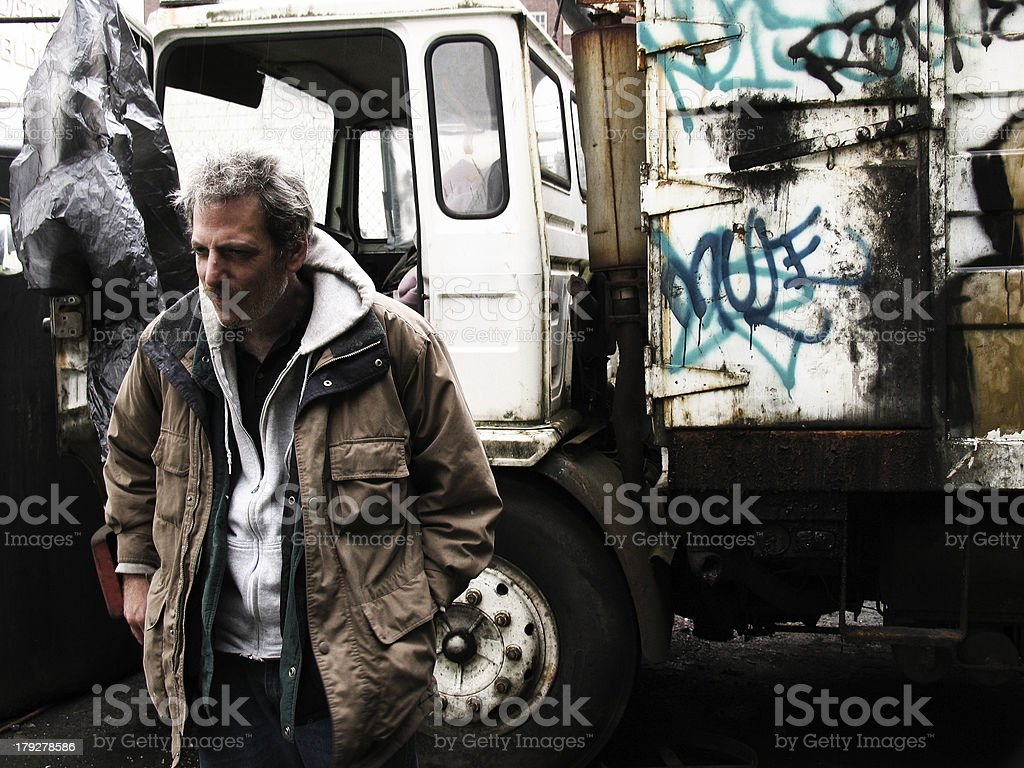 Homeless Man in Urban Scene with Old Trucks royalty-free stock photo