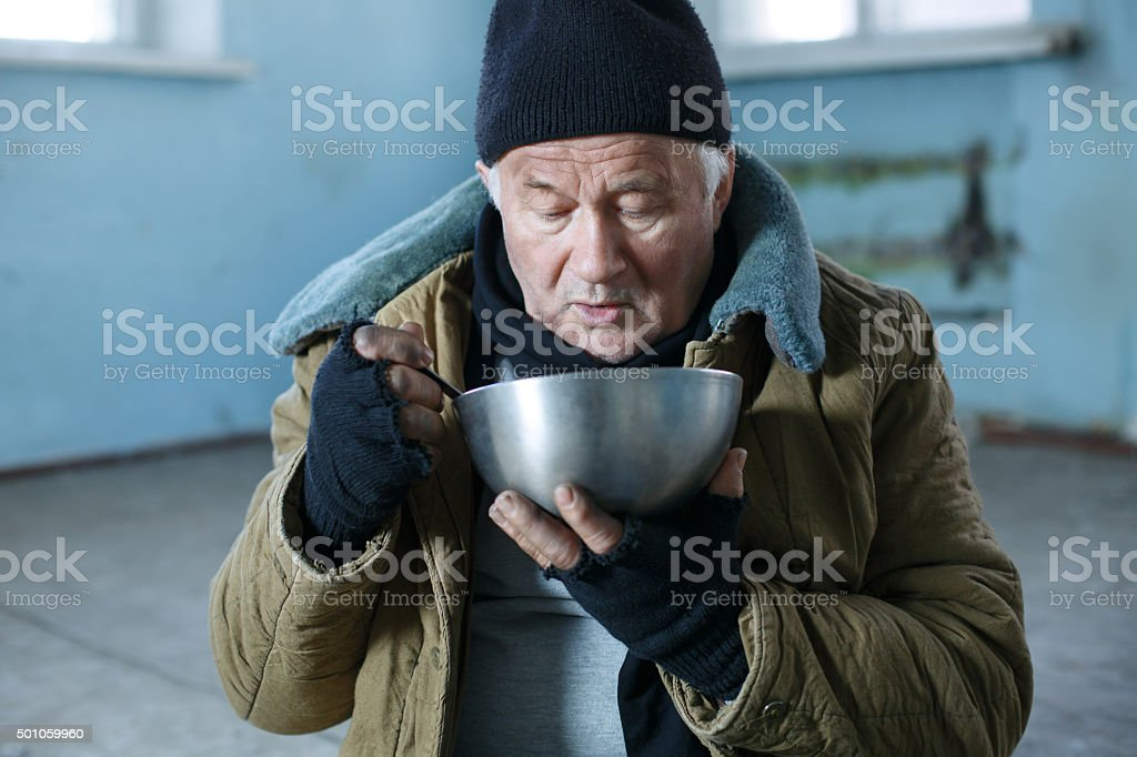Homeless man is eating from his iron bowl stock photo