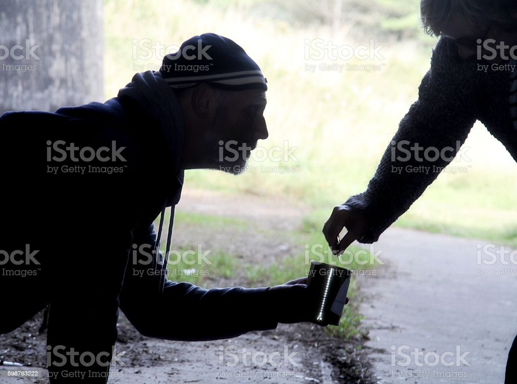 Homeless man receiving money from a passer by stock photo
