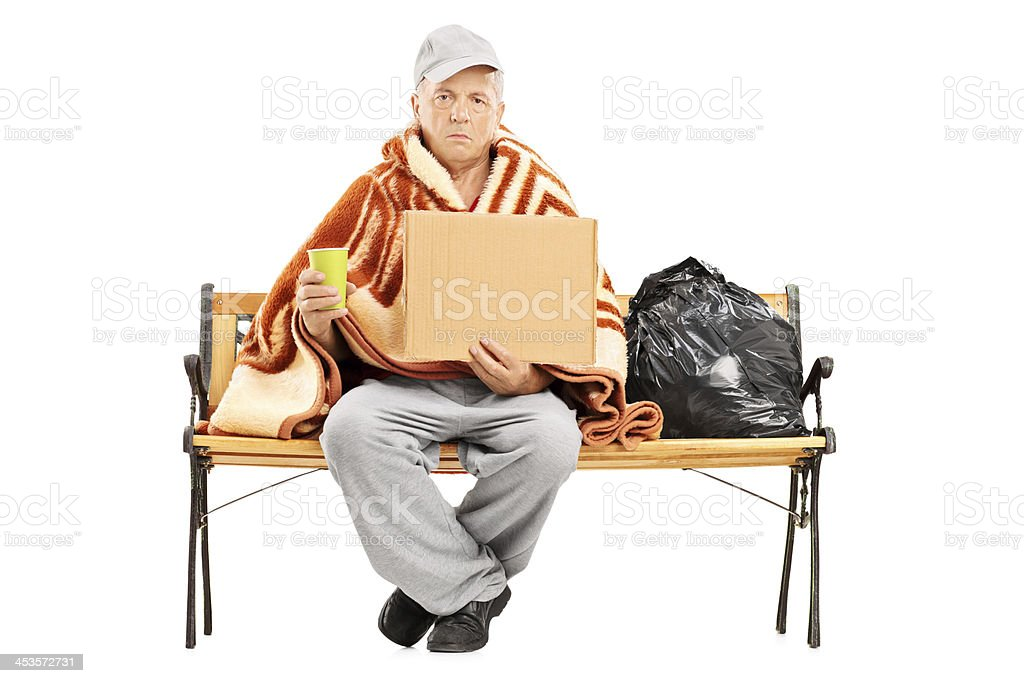 Homeless man sitting on bench and holding a cardboard royalty-free stock photo