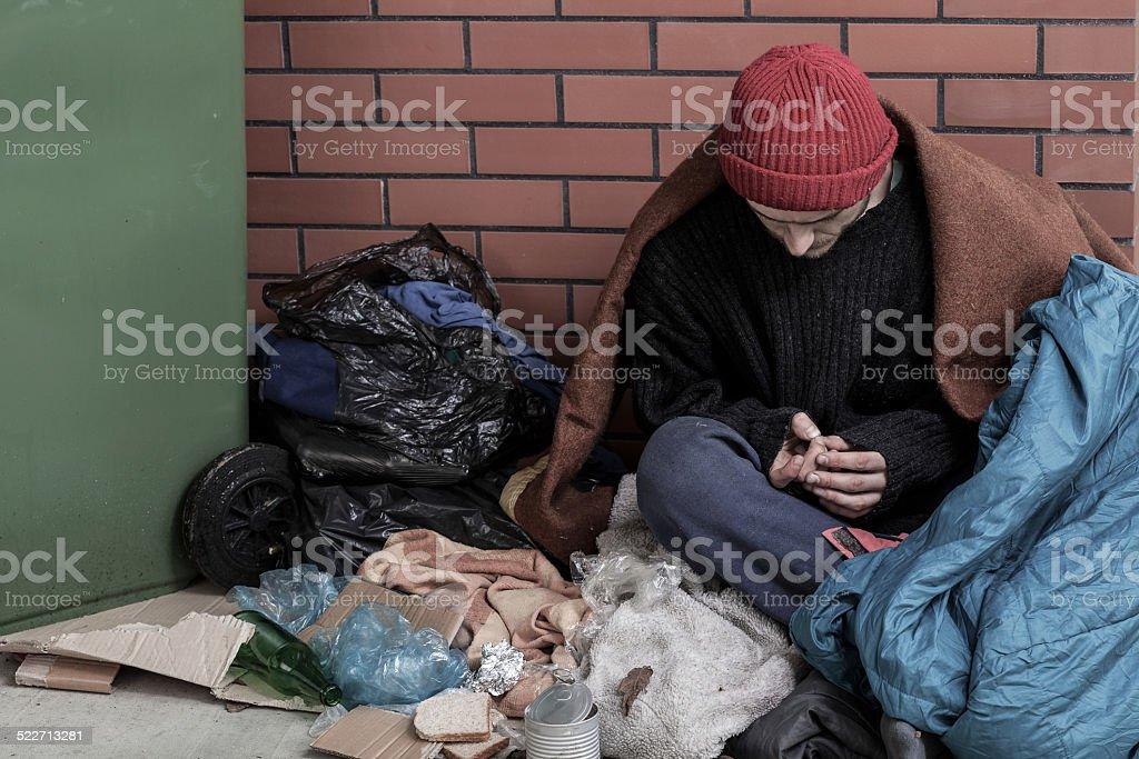Homeless man sitting on the trash stock photo