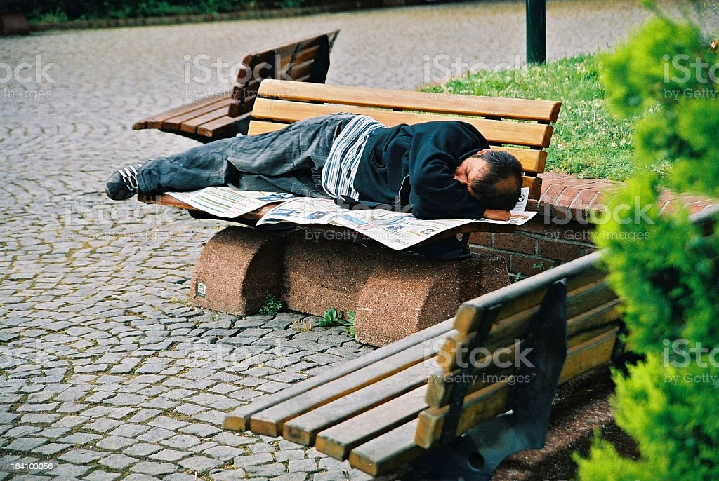 Homeless man sleeping in a park bench stock photo