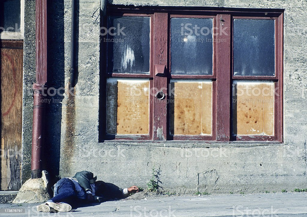 Homeless man sleeping in alley stock photo